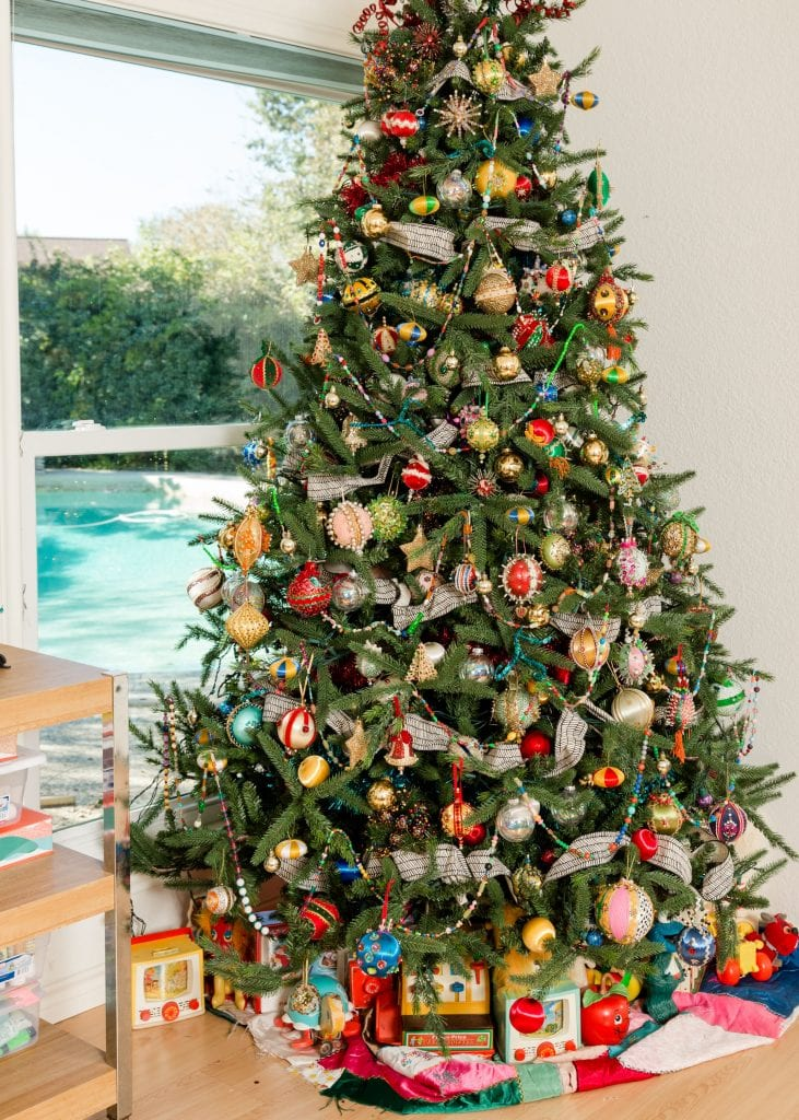Green Christmas tree with beaded ornaments and vintage toys.