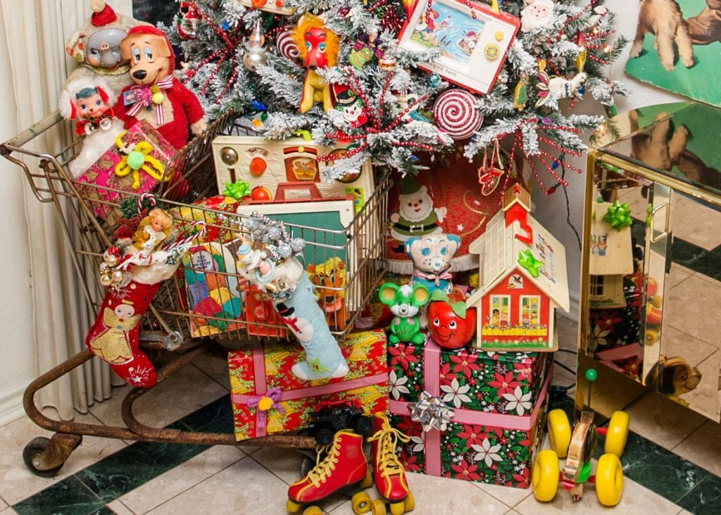Vintage sopping cart in front of a Christmas tree full of vintage toys.