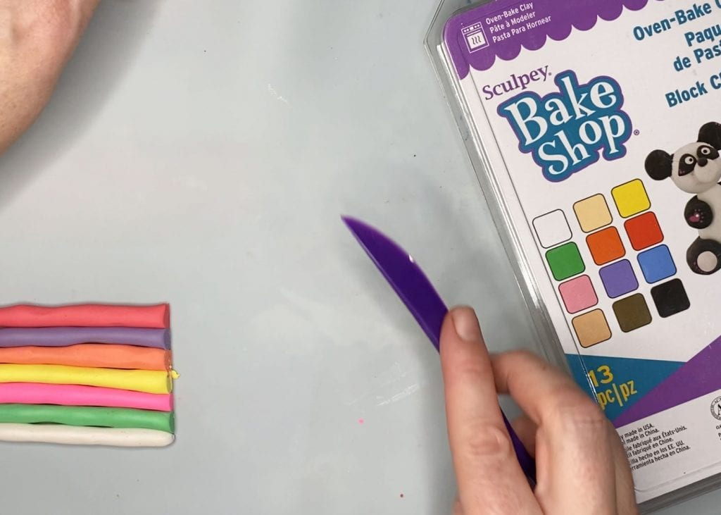 Trimming polymer clay snakes to equal lengths.