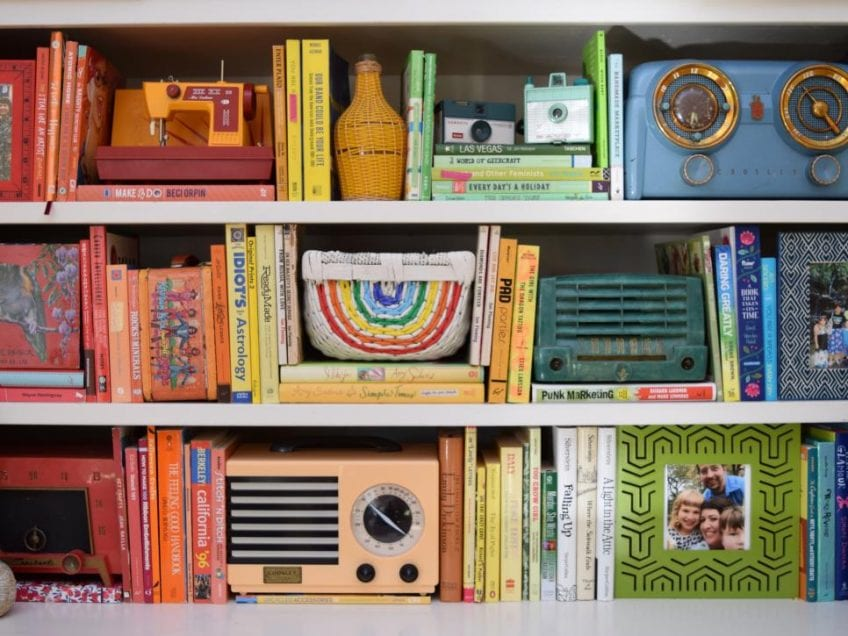 Book shelf styled in rainbow order with radios and trinkets.