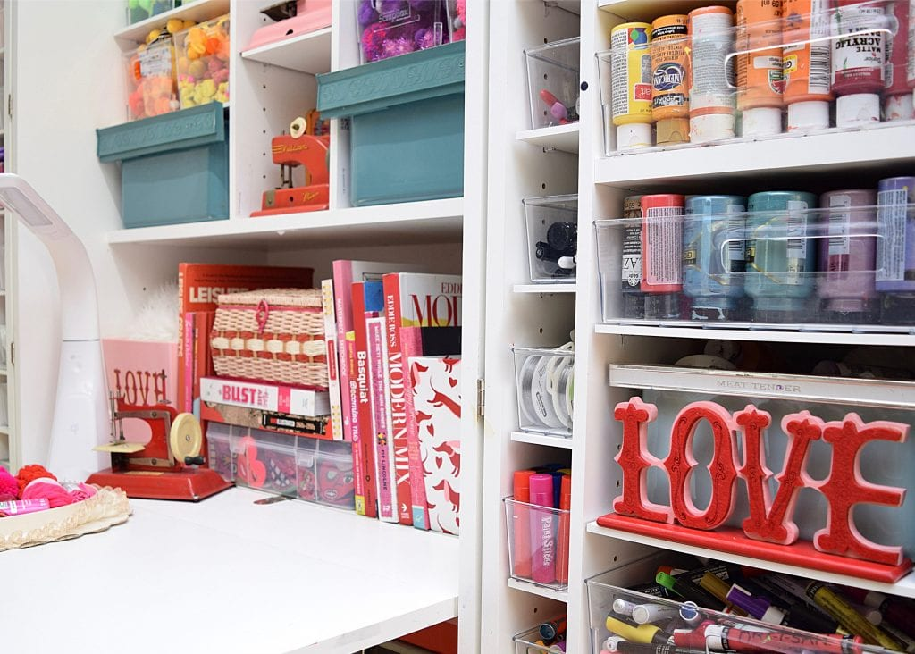 Shelves inside a craft cabinet styled for Valentine's Day.