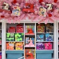 A craft space decorated for Valentine's Day with pink garlands and toy sewing machines.