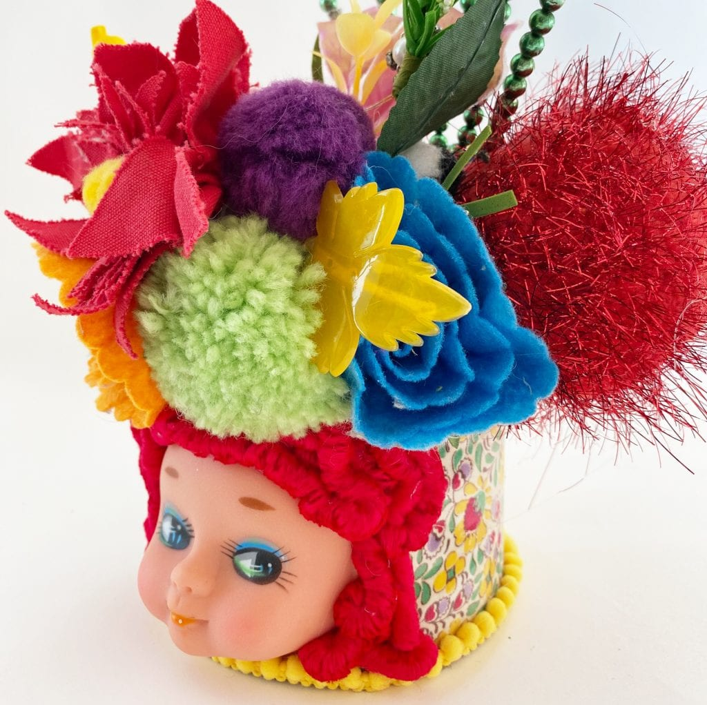 Vintage doll head vase with bouquet.